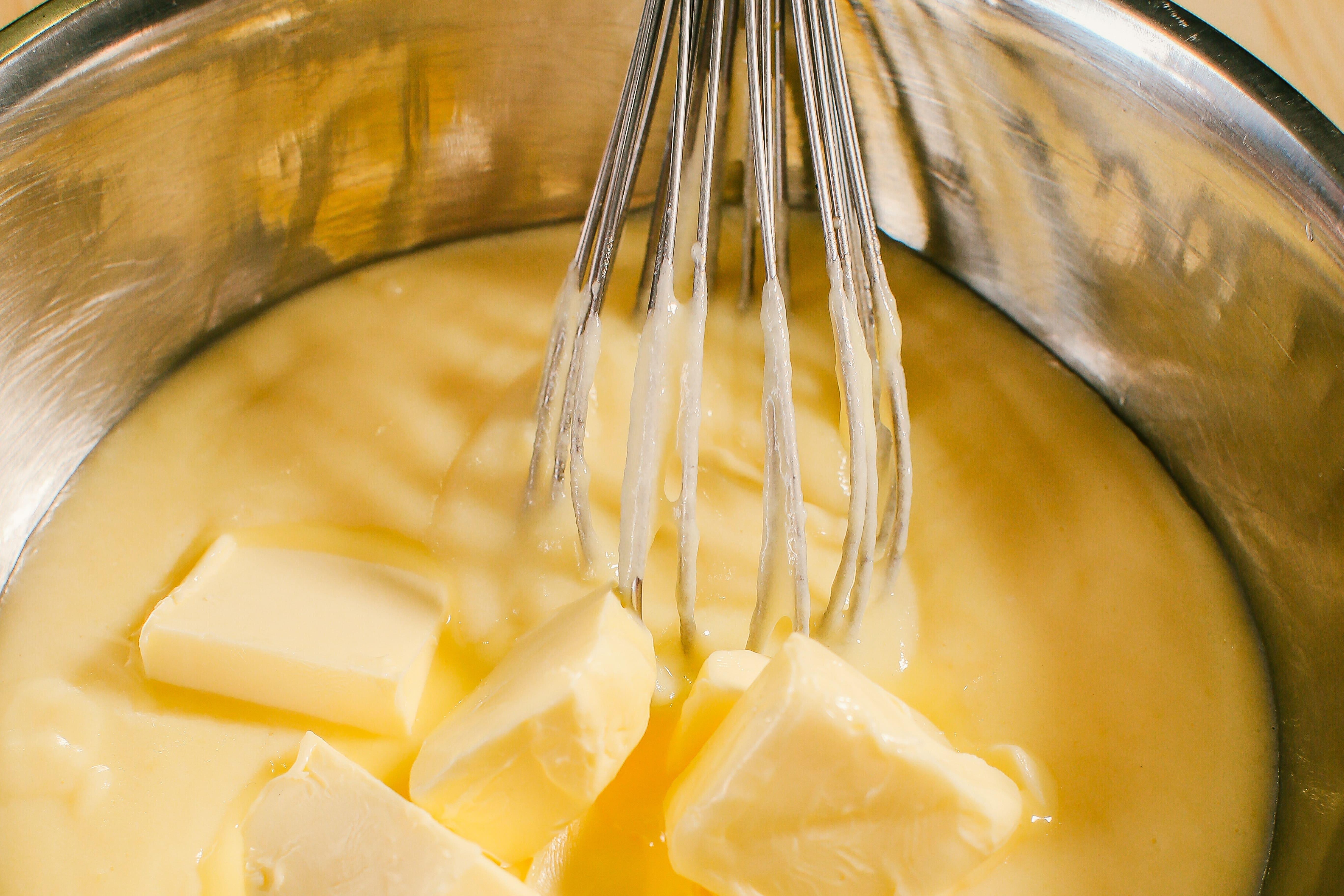 Коли крем трохи охолонув, додати холодне вершкове масло шматочками, безперервно перемішуючи вінчиком або збиваючи блендером. Накрити харчовою плівкою «в контакт» та поставити в холодильник.