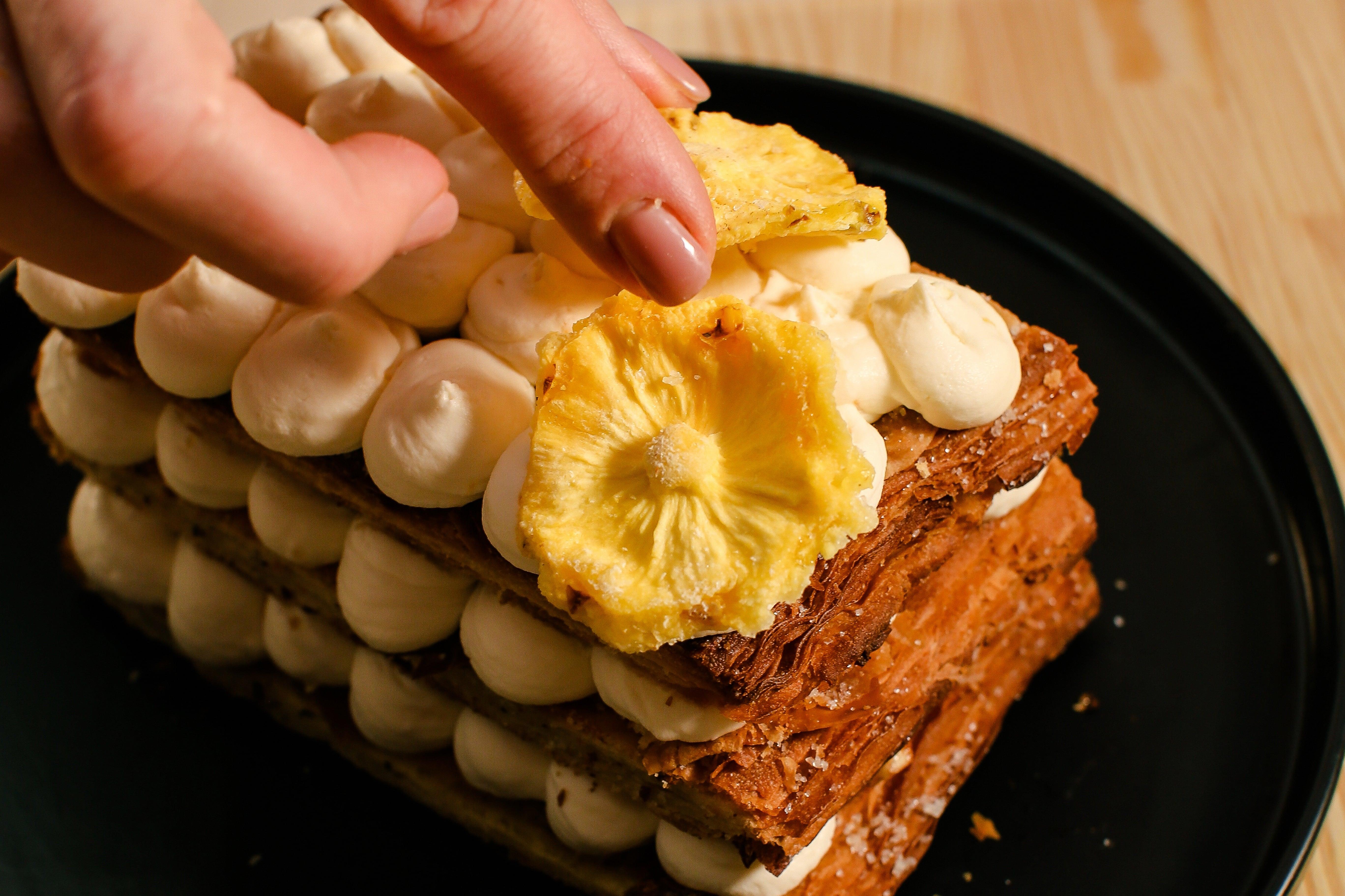 Приготувати ананасові чіпси та прикрасити ними мільфей. Для ананасових чіпсів зварити сироп – вода + цукор, довести до кипіння та проварити 4-5 хвилин. Ананас нарізати кружальцями товщиною 0,5 см. Занурити ананас в сироп,  викласти на пергаментний папір та висушити у духовій шафі за температури 110-120ºC протягом 2 годин.